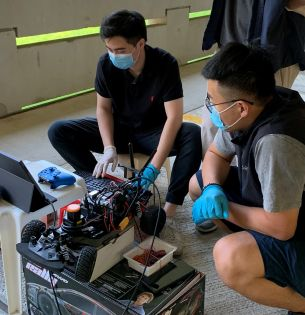 Robotics students working with car
