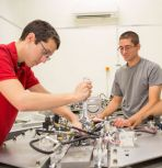 Ph.D. candidates Zachary Farley (left) and Andrew Bergey set up a test on a two-wheel, high-acceleration track, which simulates the instabilities of the fusion reactor by rotating a container filled with two fluids of different densities.